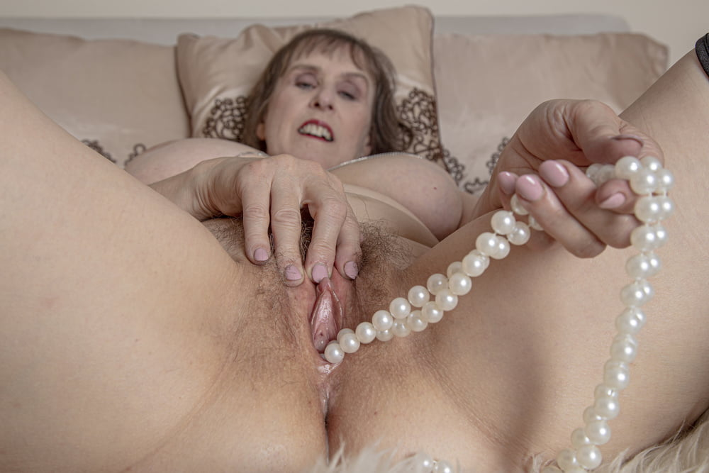 Mature Woman Wearing Beige Sweater And Pearl Necklace High