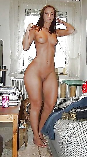 Tall blonde with great legs cups her big boobs while getting naked