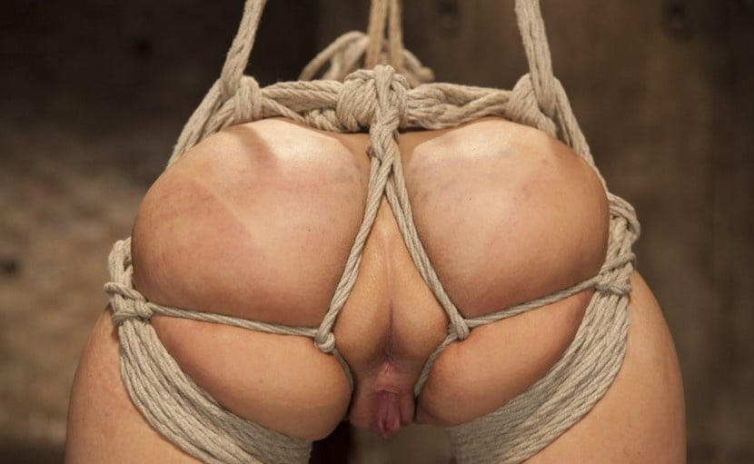 Horny slave with her legs spread and nipples tied with rope gets metal clamps on her pussy lips