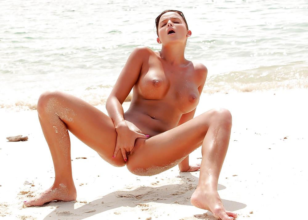 Голая телка дрочит на пляже
