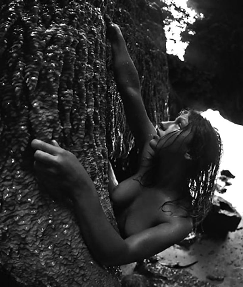 Nude woman lying on orange rocks by addictive creatives